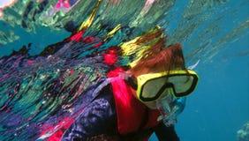 Liten flicka som snorklar dyk arkivbild