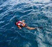 Liten flicka som snorklar i havet Arkivfoto