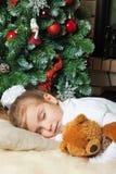 Liten flicka som sovar nära jultree Arkivbilder