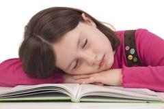 Liten flicka som sovar på ett öppet, bokar Royaltyfria Bilder