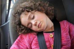 Liten flicka som sover i ett bilsäte Royaltyfri Bild