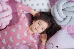 Liten flicka som sover i kuddarna Arkivfoto