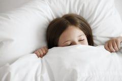 Liten flicka som sover i säng arkivbilder