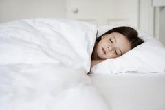 Liten flicka som sover i säng royaltyfria foton