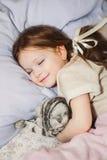 Liten flicka som sover i säng med hennes katt Arkivbild