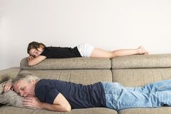 Liten flicka som sover med hennes farsa på soffan royaltyfria bilder
