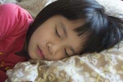 Liten flicka som sover på säng Royaltyfri Bild