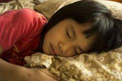 Liten flicka som sover på säng Royaltyfri Foto