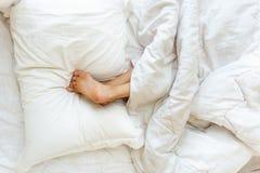 Liten flicka som sover uppochnervänd och hållande fot på kudden royaltyfri fotografi