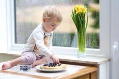 Liten flicka som spelar äta inomhus smakliga pannkakor Royaltyfri Foto