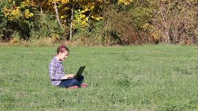 Liten flicka som spelar bärbara datorn i parkerahöstsäsongen stock video