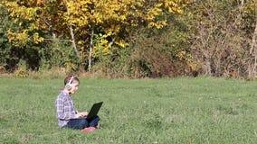 Liten flicka som spelar bärbara datorn och lyssnande musik på hörlurar stock video