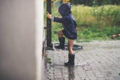 Liten flicka som spelar den ensamma yttersidan i dåligt väder Royaltyfri Foto