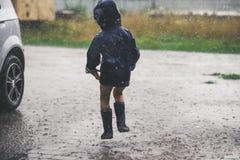 Liten flicka som spelar den ensamma yttersidan i dåligt väder Arkivfoto