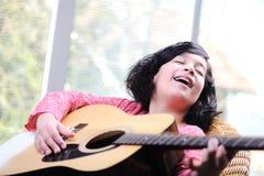 Liten flicka som spelar gitarren arkivbild