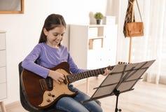 Liten flicka som spelar gitarren på musikkursen royaltyfri bild