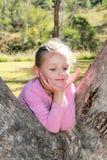 Liten flicka som spelar i en eukalyptusträd Fotografering för Bildbyråer