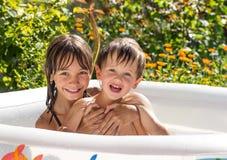 Liten flicka som spelar i en uppblåsbar pöl med hans yngre bror som blandar Royaltyfria Bilder