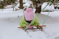 liten flicka som spelar i gatan i vinter arkivbild