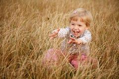 Liten flicka som spelar i gräset Arkivfoto