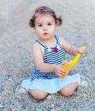 Liten flicka som spelar i sanden med en kratta arkivfoto