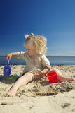Liten flicka som spelar i sanden på stranden vid havet royaltyfria bilder