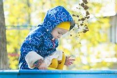 Liten flicka som spelar i sandlåda utomhus på höstgulingbuskaget och trädsidabakgrund fotografering för bildbyråer