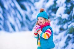 Liten flicka som spelar i snöig vinterskog Fotografering för Bildbyråer