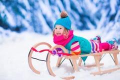 Liten flicka som spelar i snöig vinterskog Arkivbilder