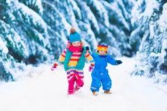 Liten flicka som spelar i snöig vinterskog Arkivfoton