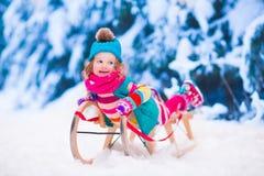 Liten flicka som spelar i snöig vinterskog Royaltyfri Bild