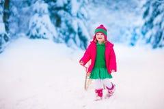 Liten flicka som spelar i snöig vinterskog Arkivbild