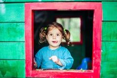 Liten flicka som spelar i trähus i natur royaltyfri bild