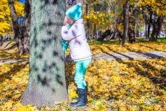 Liten flicka som spelar kurragömma nära trädet in Arkivfoton