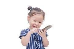 Liten flicka som spelar leken på mobiltelefonen Arkivbilder