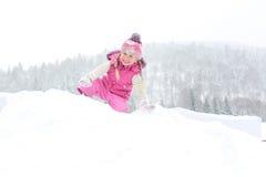 Liten flicka som spelar lyckligt i snön Arkivbild