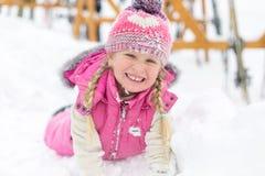 Liten flicka som spelar lyckligt i snön Fotografering för Bildbyråer