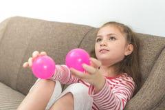 Liten flicka som spelar med bollen på soffan Royaltyfri Bild