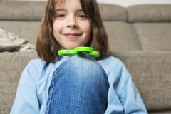 Liten flicka som spelar med den gröna rastlös människaspinnareleksaken Royaltyfria Foton