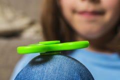 Liten flicka som spelar med den gröna rastlös människaspinnareleksaken Royaltyfri Fotografi
