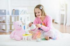 Liten flicka som spelar med dockhuset Unge med leksaker fotografering för bildbyråer