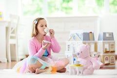 Liten flicka som spelar med dockhuset Unge med leksaker arkivbilder