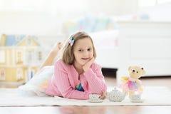 Liten flicka som spelar med dockhuset Unge med leksaker arkivbild