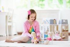 Liten flicka som spelar med dockhuset Unge med leksaker royaltyfria bilder
