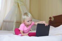Liten flicka som spelar med en bärbar dator på den stora sängen royaltyfri fotografi