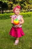 Liten flicka som spelar med en boll arkivbild