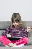 Liten flicka som spelar med en digital minnestavla Arkivfoto