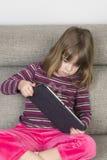 Liten flicka som spelar med en digital minnestavla Royaltyfri Foto