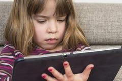 Liten flicka som spelar med en digital minnestavla Arkivfoton