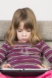Liten flicka som spelar med en digital minnestavla Arkivbilder